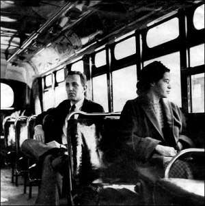 Rosa Parks on a Montgomery bus on December 21, 1956, the day Montgomery's public transportation system was legally integrated. Behind Parks is Nicholas C. Chriss, a reporter covering the event. United Press photo